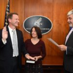 Left to right: Dr. Sharpless (joined by his wife, Julie Lund Sharpless, MD), is sworn in as NCI director by Acting Secretary of Health and Human Services' Eric D. Hargan.