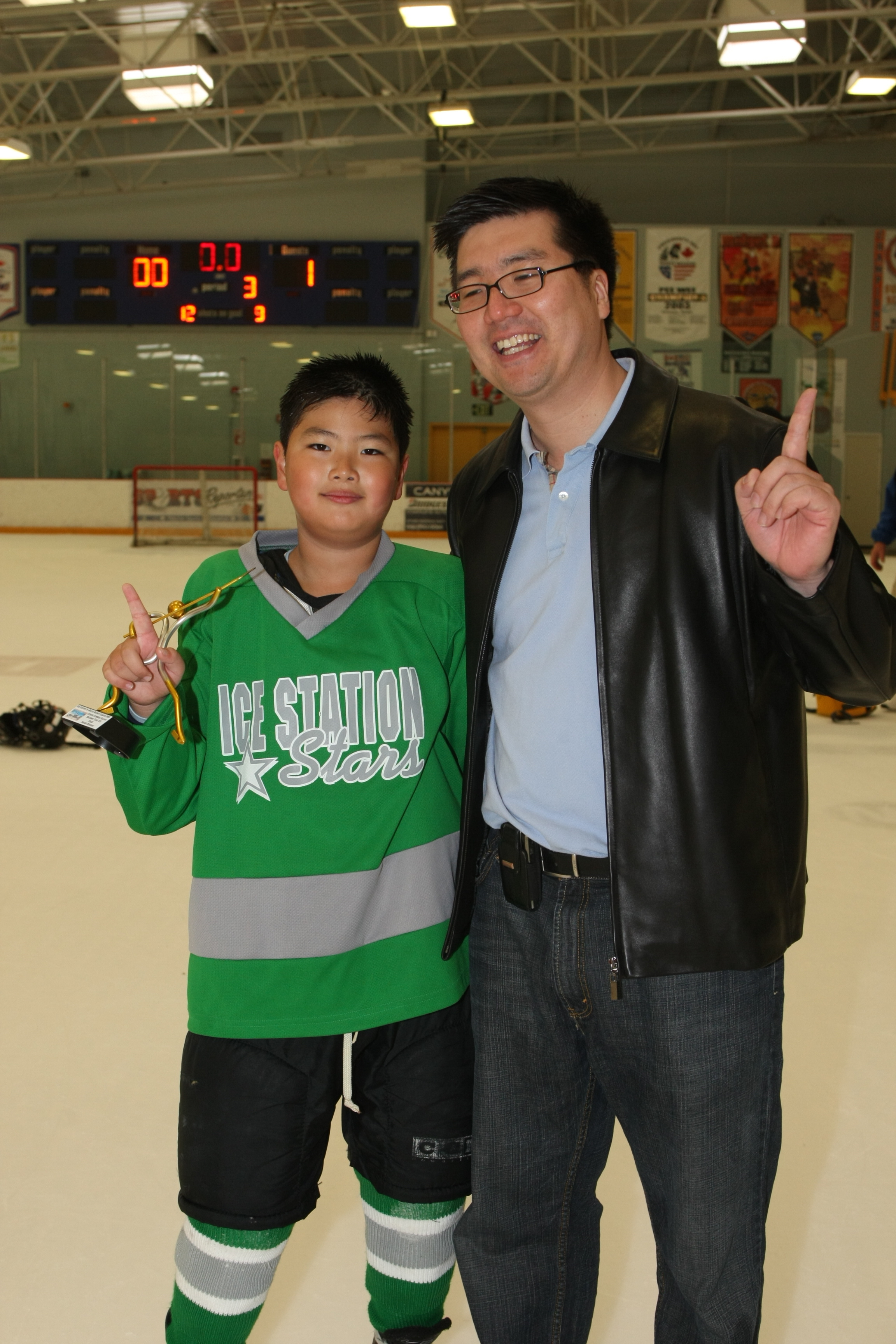 Dr. Yang (coach of the Ice Station Stars) and his son celebrate a recent win.